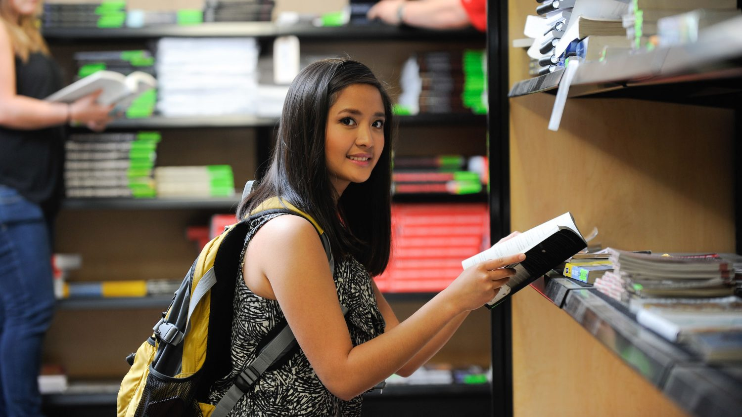 A student looks through books at the book store.
