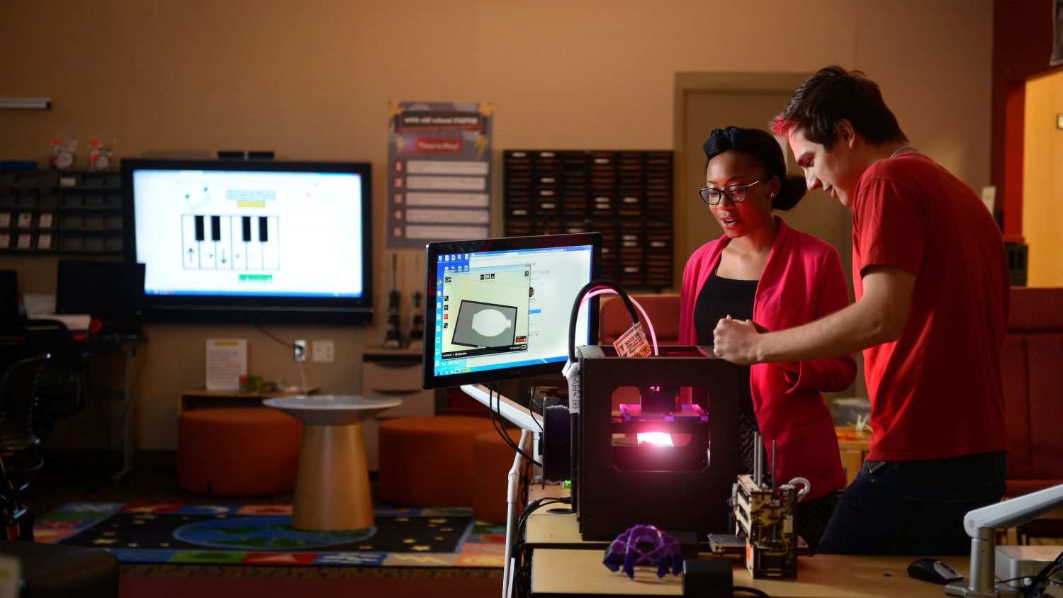 College of education students work in the library at Poe Hall with a Makerbot 3D printer.